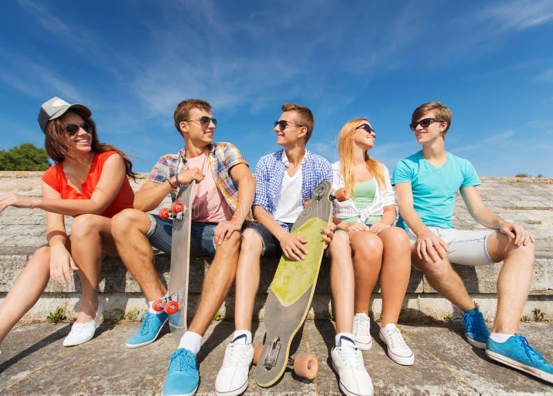 Gruppo di amici sorridenti che si siedono sulla via della città fotografie stock