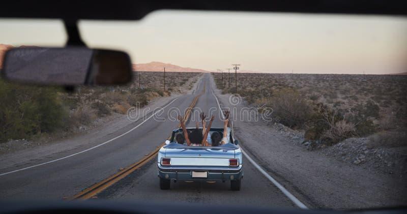 Gruppo di amici sul viaggio stradale che conduce automobile convertibile classica osservata tramite il parabrezza di seguente vei fotografia stock libera da diritti