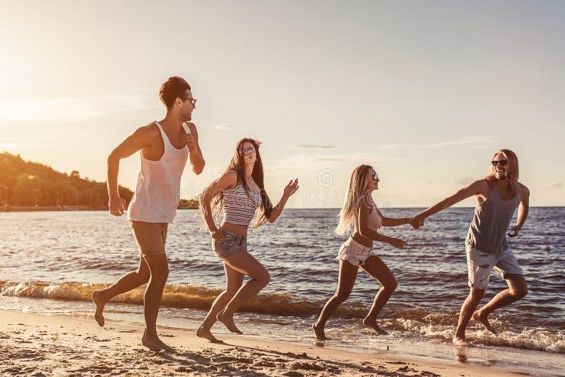 Gruppo di amici sulla spiaggia immagine stock
