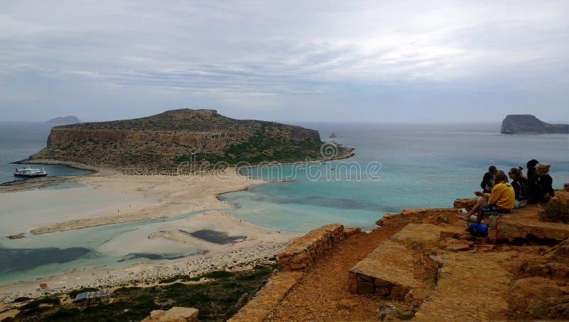 Gruppo di amico-turisti che si siedono sulla collina vicino a Balos, chiacchieranti e pieni d'ammirazione le belle viste Resto e  fotografia stock libera da diritti