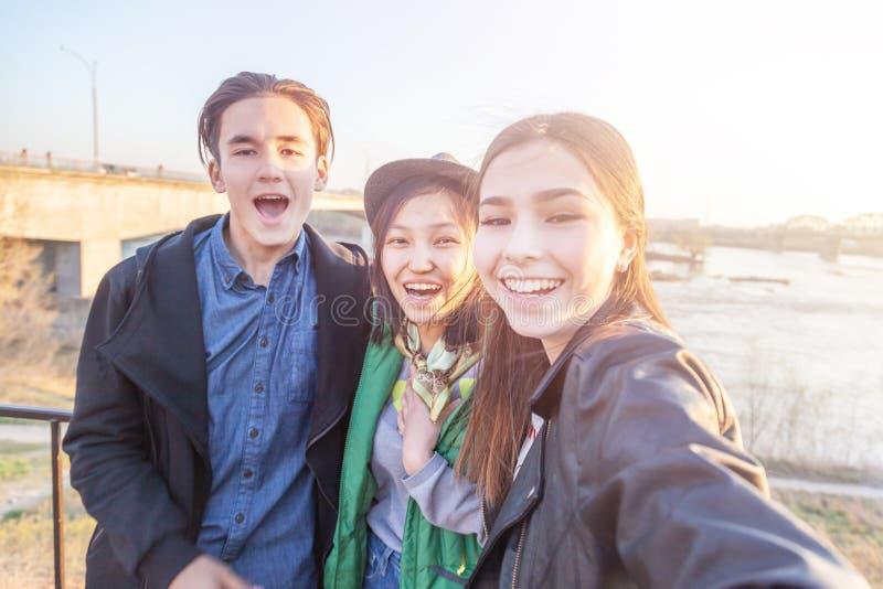 Gruppo di anni dell'adolescenza asiatici che prendono selfie sul telefono, divertiresi, sui migliori amici e sul concetto digital immagine stock libera da diritti