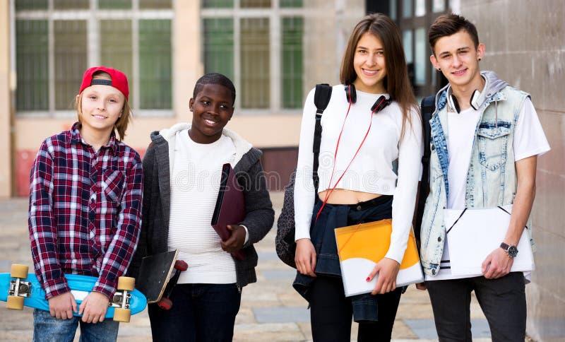 Gruppo di anni dell'adolescenza che posano scuola esterna immagine stock