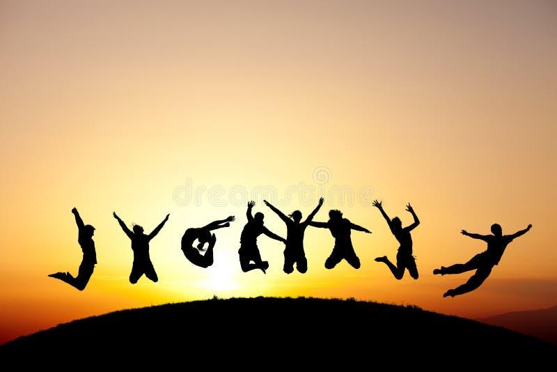 Gruppo di anni dell'adolescenza che saltano nel tramonto fotografia stock libera da diritti