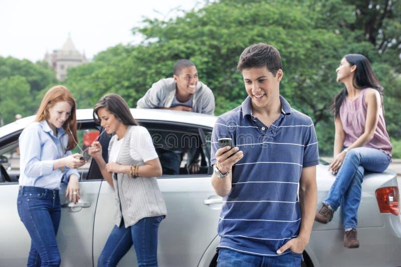 Gruppo di anni dell'adolescenza con l'automobile fotografie stock
