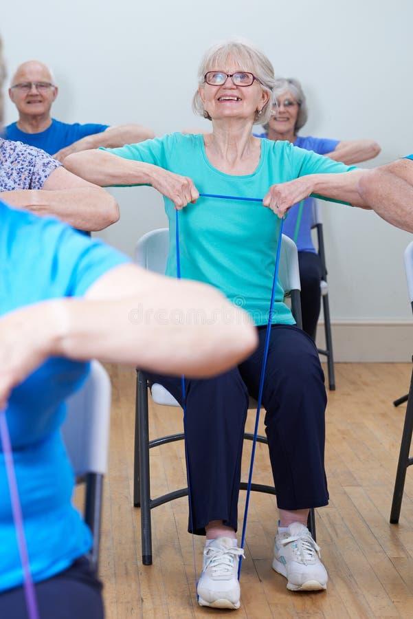 Gruppo di anziani che utilizzano le bande di resistenza nella classe di forma fisica fotografie stock
