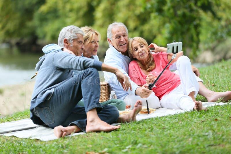 Gruppo di anziani felici che hanno picnic che prende il ricordo del selfie immagine stock