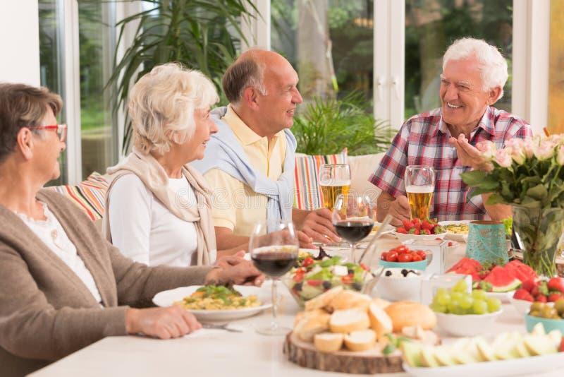 Gruppo di anziani felici che mangiano una cena immagine stock libera da diritti