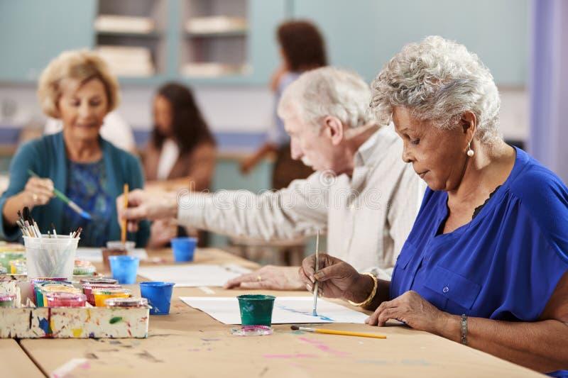 Gruppo di anziani pensionati che assistono ad Art Class In Community Centre con l'insegnante fotografie stock libere da diritti