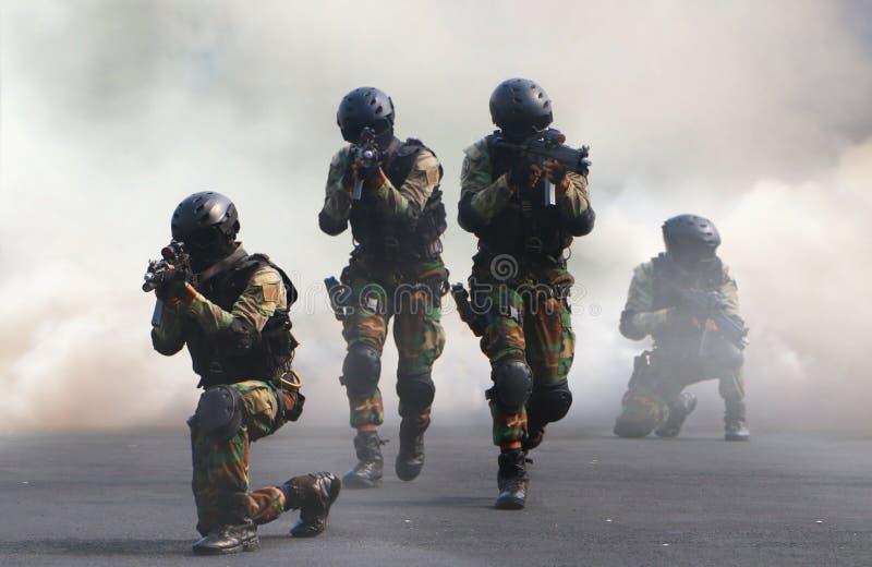 Gruppo di assalto della forza speciale nell'ambito del fondo di cortina di fumo fotografie stock libere da diritti