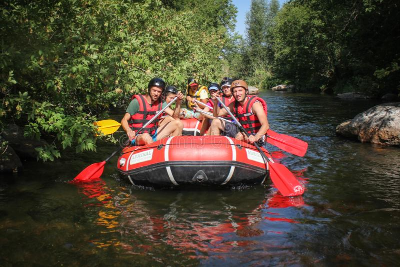 Gruppo di avventuriere che gode che trasporta fiume con una zattera immagini stock