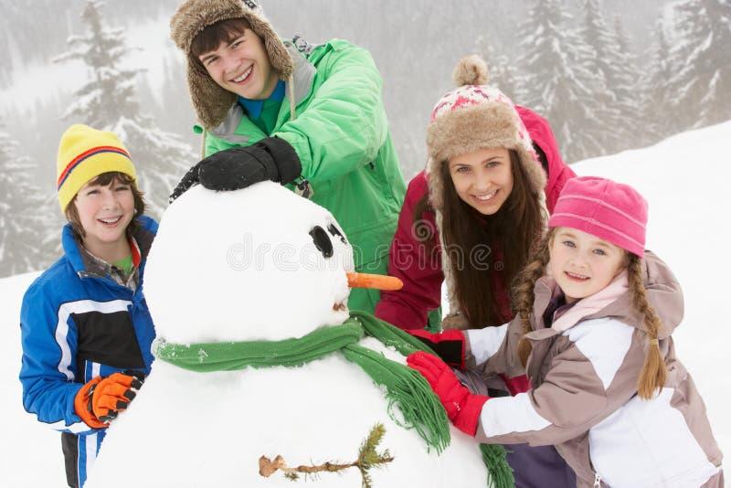 Gruppo di bambini che costruiscono pupazzo di neve sulla festa del pattino fotografie stock