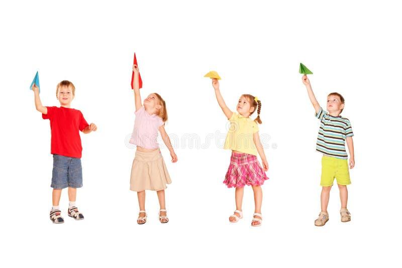 Gruppo di bambini che giocano con gli aeroplani di carta fotografie stock