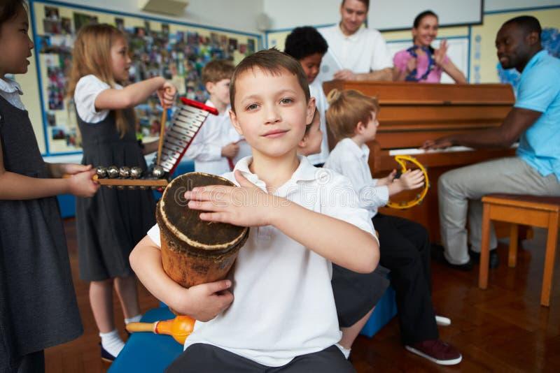Gruppo di bambini che giocano insieme nell'orchestra della scuola fotografie stock