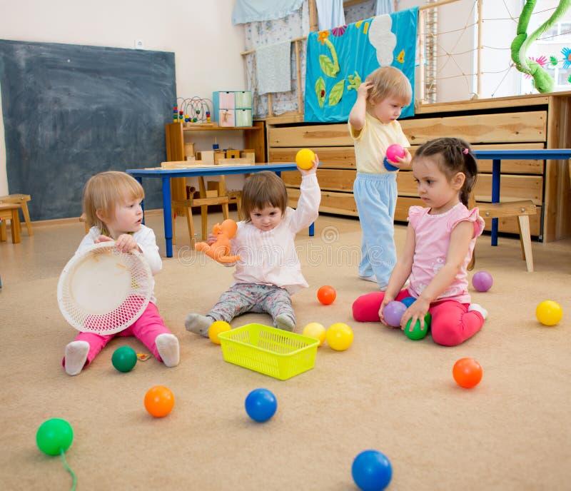 Gruppo di bambini che giocano le palle nel centro di guardia o di asilo immagini stock libere da diritti