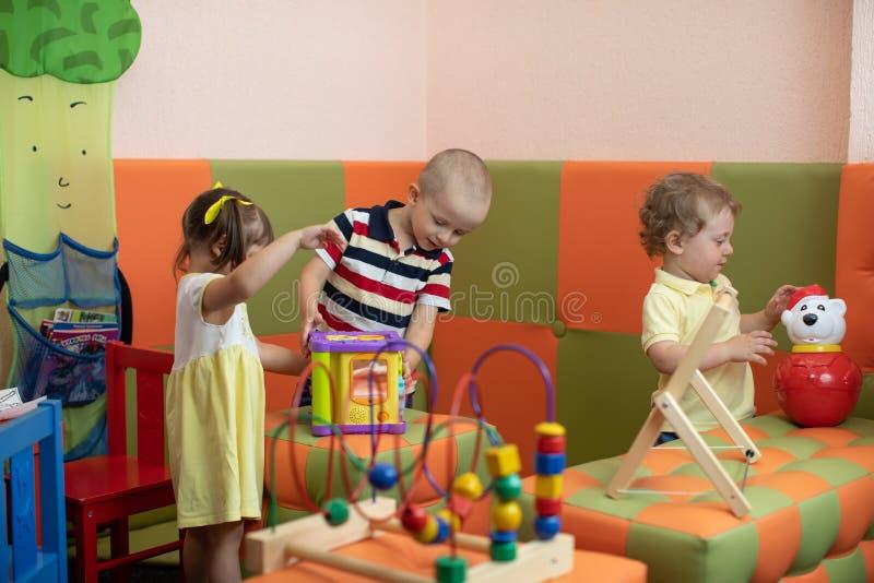 Gruppo di bambini che giocano nel centro di guardia o di asilo immagini stock libere da diritti