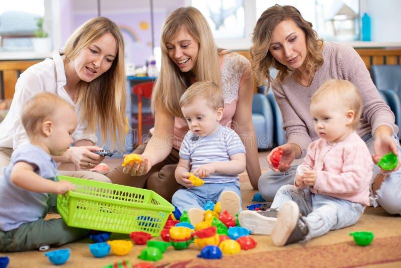 Gruppo di bambini che giocano nel centro di guardia o di asilo sotto la supervisione delle mamme immagini stock libere da diritti