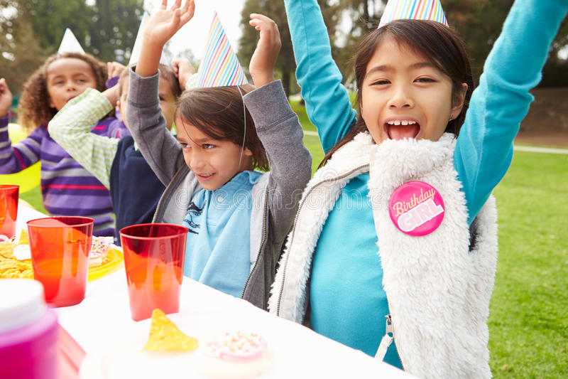 Gruppo di bambini che hanno festa di compleanno all'aperto immagine stock