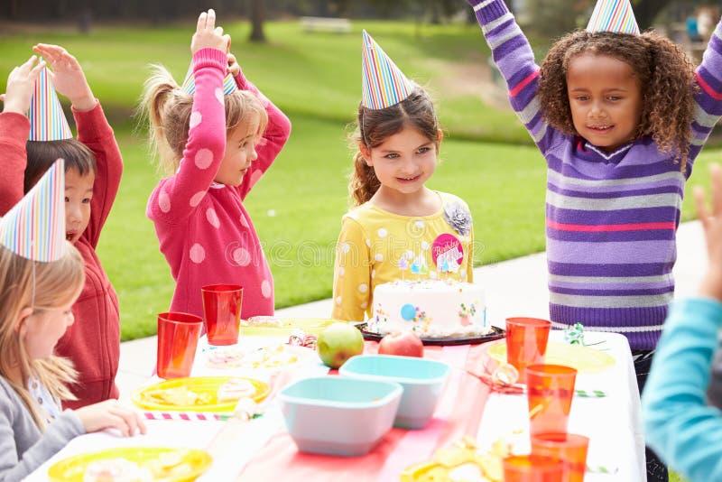 Gruppo di bambini che hanno festa di compleanno all'aperto fotografia stock libera da diritti