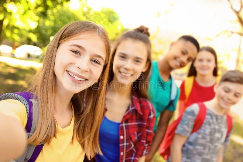 Gruppo di bambini che prendono selfie all'aperto immagini stock libere da diritti
