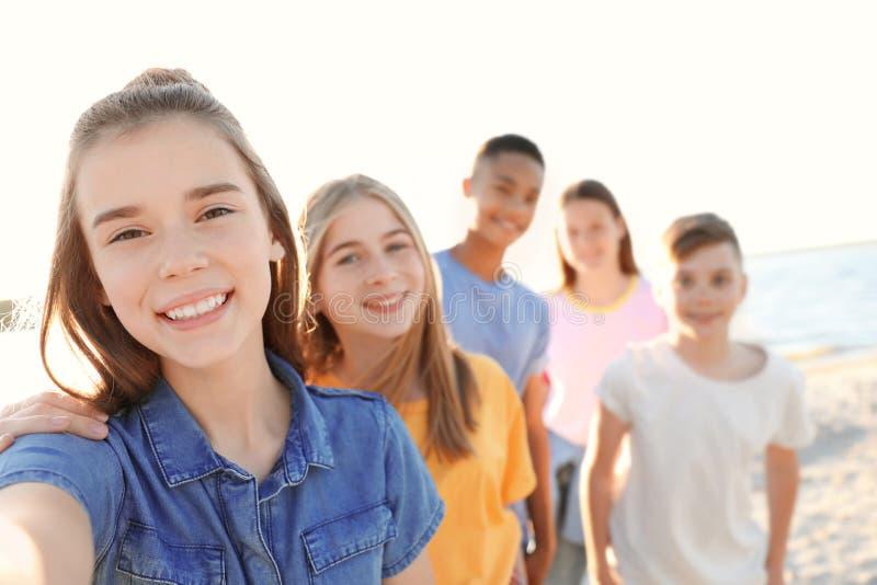 Gruppo di bambini che prendono selfie sulla spiaggia immagini stock libere da diritti