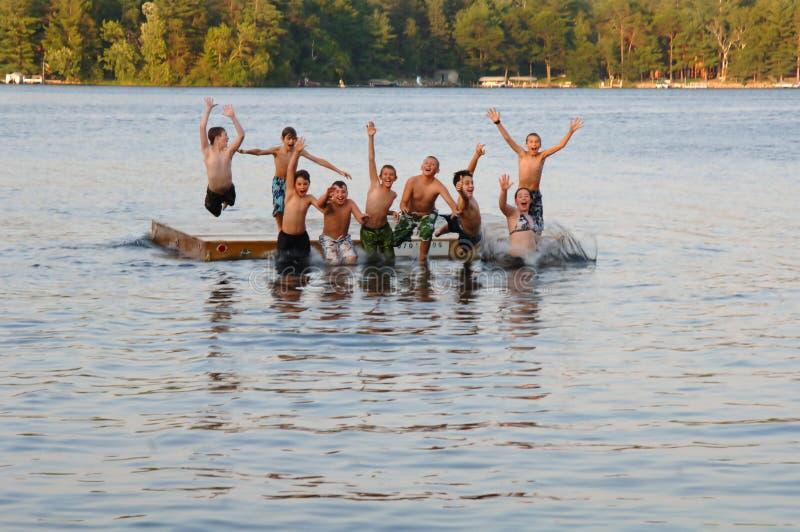 Gruppo di bambini che saltano nel lago fotografia stock