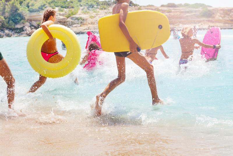 Gruppo di bambini che si imbattono in mare per nuotare fotografie stock