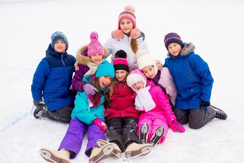 Gruppo di bambini che si siedono sul ghiaccio fotografie stock
