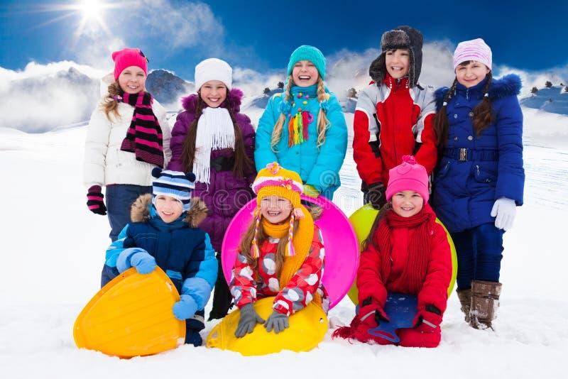 Gruppo di bambini con le slitte fotografia stock