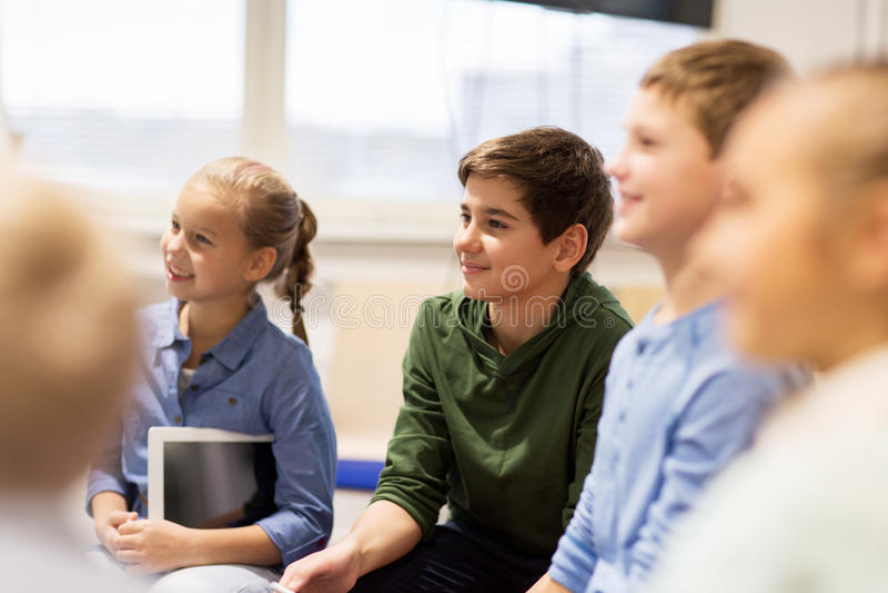 Gruppo di bambini o di amici felici che imparano alla scuola immagini stock libere da diritti