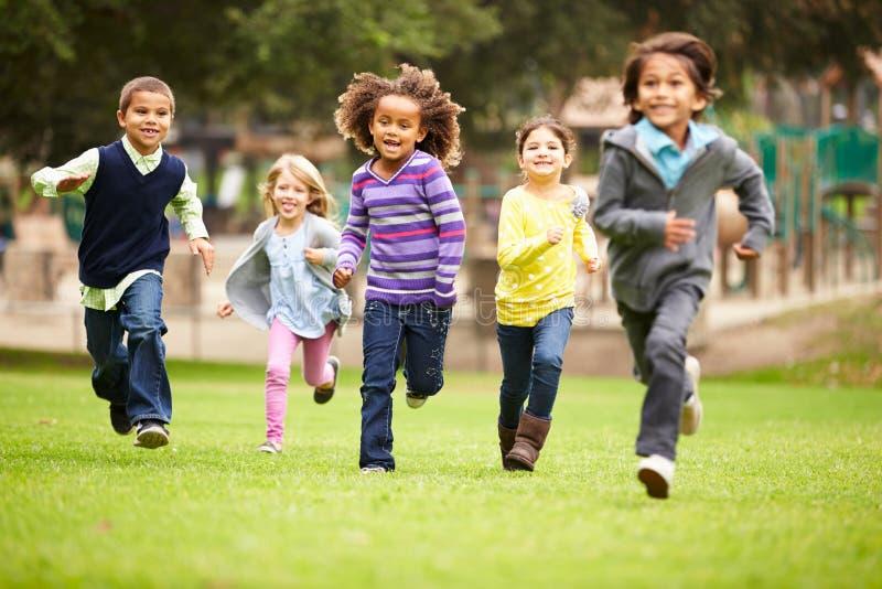 Gruppo di bambini piccoli che corrono verso la macchina fotografica in parco immagini stock libere da diritti