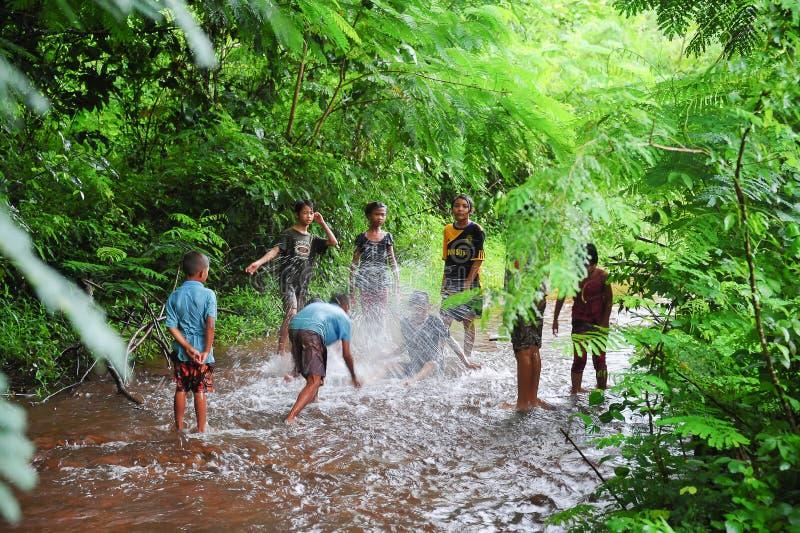 Gruppo di bambini rurali che giocano insieme in acqua fotografia stock