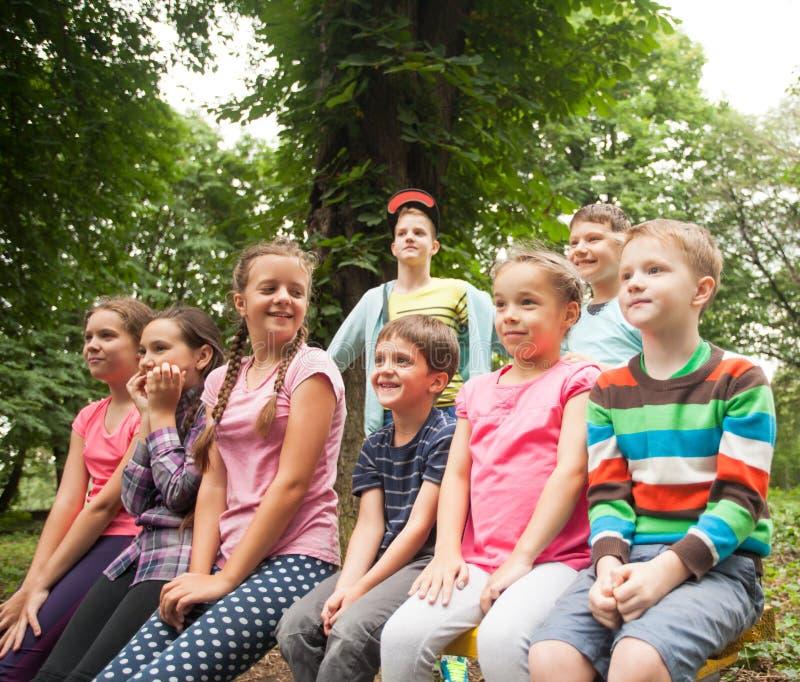 Gruppo di bambini su un banco di parco fotografie stock