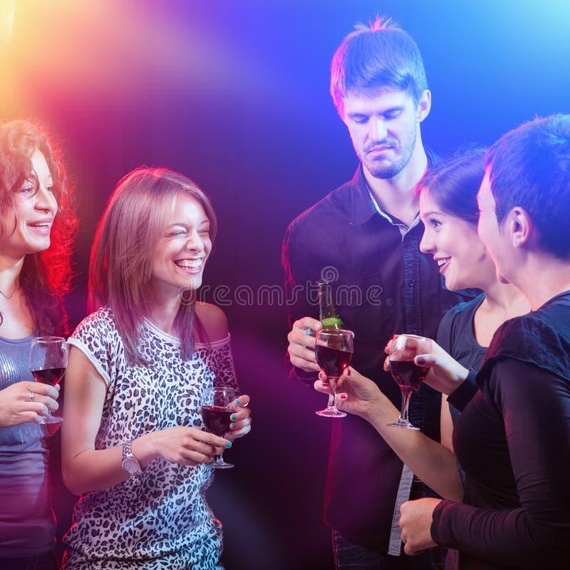 Gruppo di bei giovani amici al night-club. immagine stock