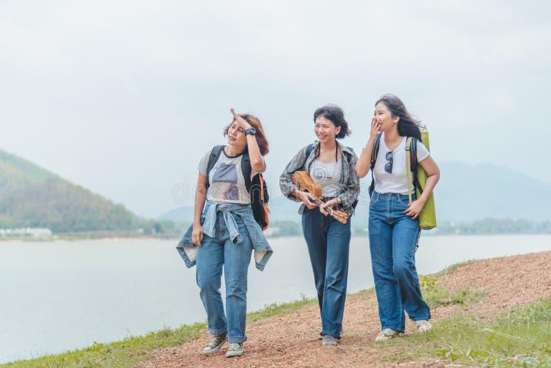 Gruppo di belle giovani donne che camminano nella foresta, godente della vacanza, del concetto di viaggio, della morbidezza e del fotografia stock libera da diritti