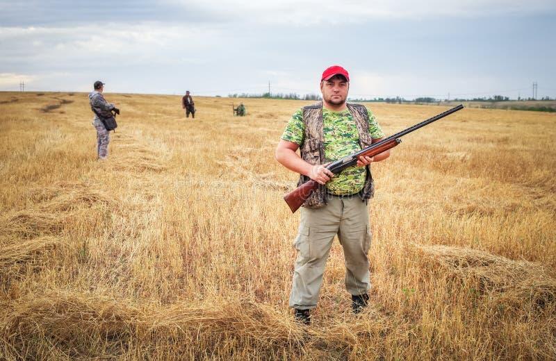 Gruppo di cacciatori con le pistole che si muovono attraverso il campo immagine stock
