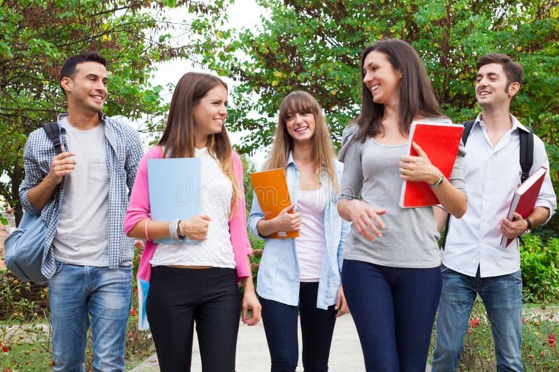 Gruppo di camminata sorridente degli studenti all'aperto immagini stock libere da diritti