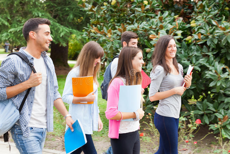 Gruppo di camminata sorridente degli studenti all'aperto fotografia stock