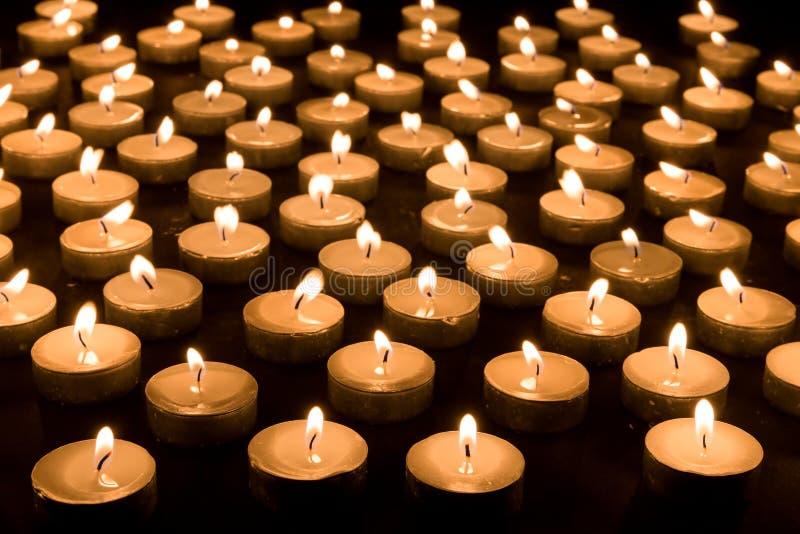 Gruppo di candele brucianti ad un fondo nero immagini stock