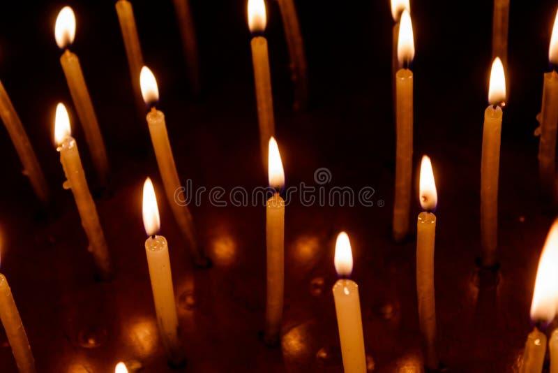 Gruppo di candele brucianti nello scuro fotografia stock libera da diritti
