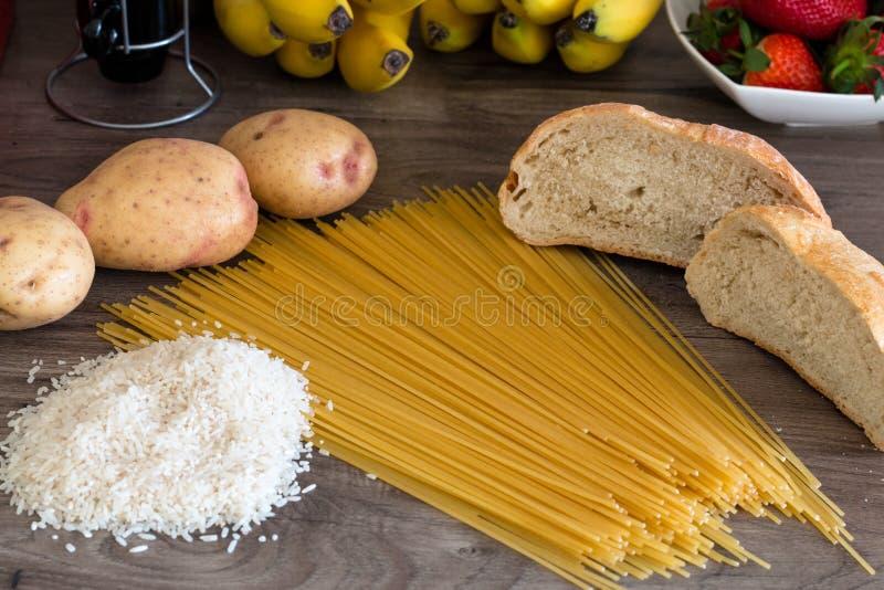 Gruppo di carboidrati per la dieta - pane, riso, patate e pasta su una tavola di legno fotografia stock libera da diritti