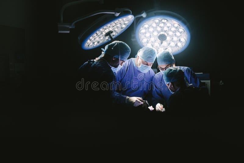Gruppo di chirurghi al teatro in funzione del lavoro immagini stock libere da diritti