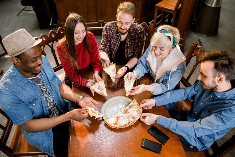 Gruppo di cinque amici multiethnical allegri che mangiano pizza deliziosa mentre riunito in piccolo caffè adorabile fotografie stock