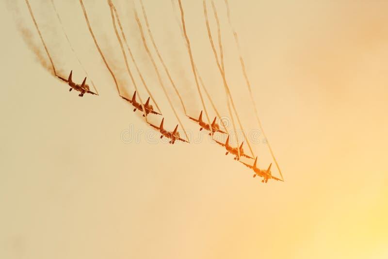 Gruppo di combattenti nel cielo arancio con una traccia di fumo nero e le tracce di nuvole bianche di vortice del vapore fotografia stock libera da diritti
