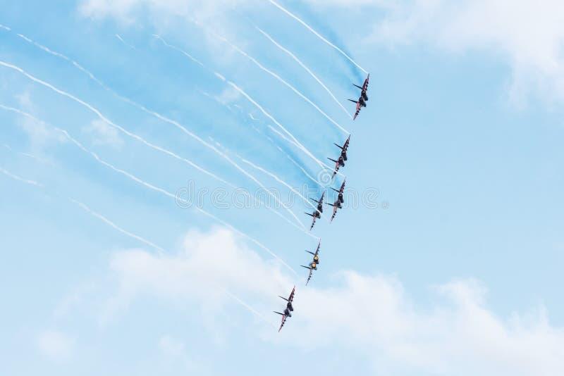 Gruppo di combattenti nel cielo blu con una traccia di fumo nero e le tracce di nuvole bianche di vortice del vapore immagini stock