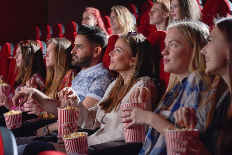 Gruppo di commedia di sorveglianza femminile in cinema immagine stock libera da diritti