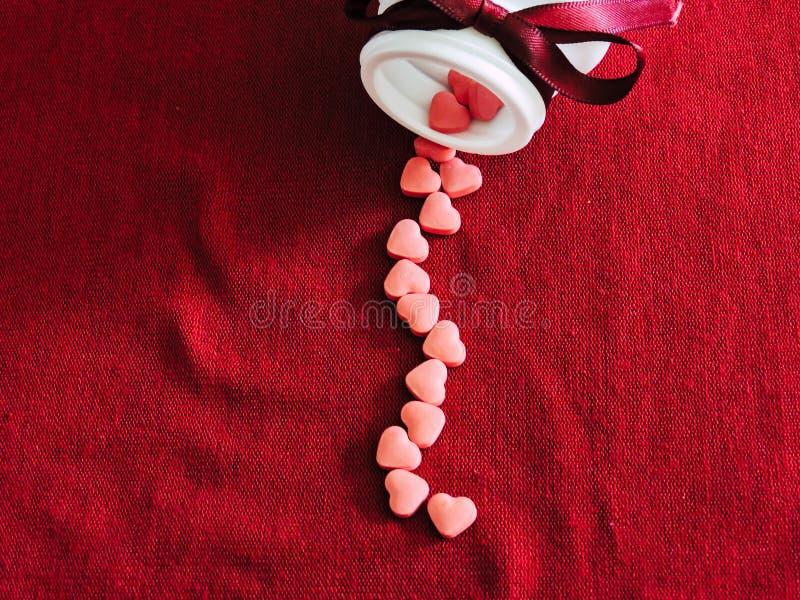 Gruppo di compresse dei cuori sul fondo rosso del panno Rosa rossa immagini stock