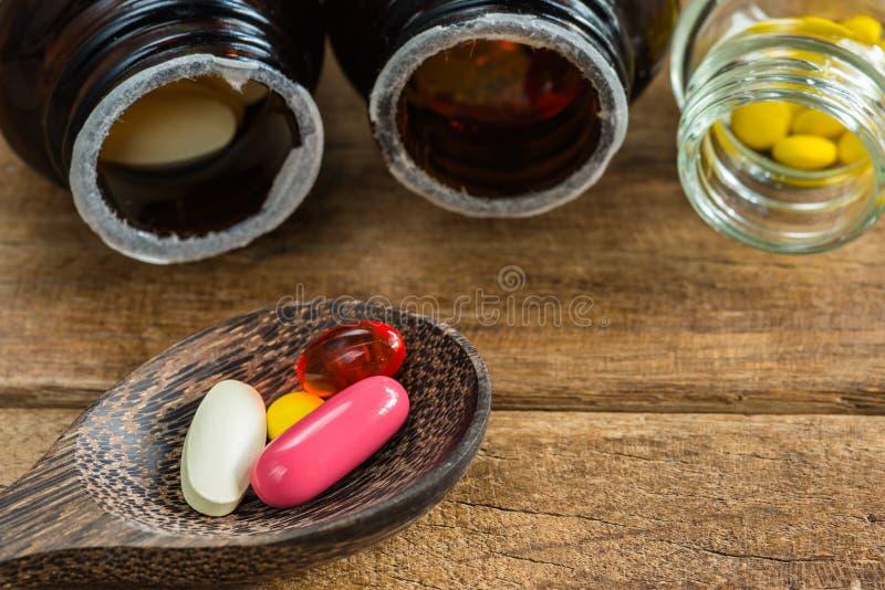 Gruppo di compresse supplementari della vitamina in cucchiaio di legno sulla tavola di legno fotografie stock
