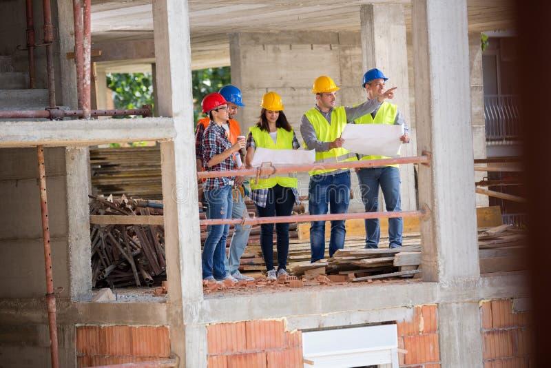 Gruppo di controllo al posto di manifestazione della costruzione di edifici di costruzione fotografia stock