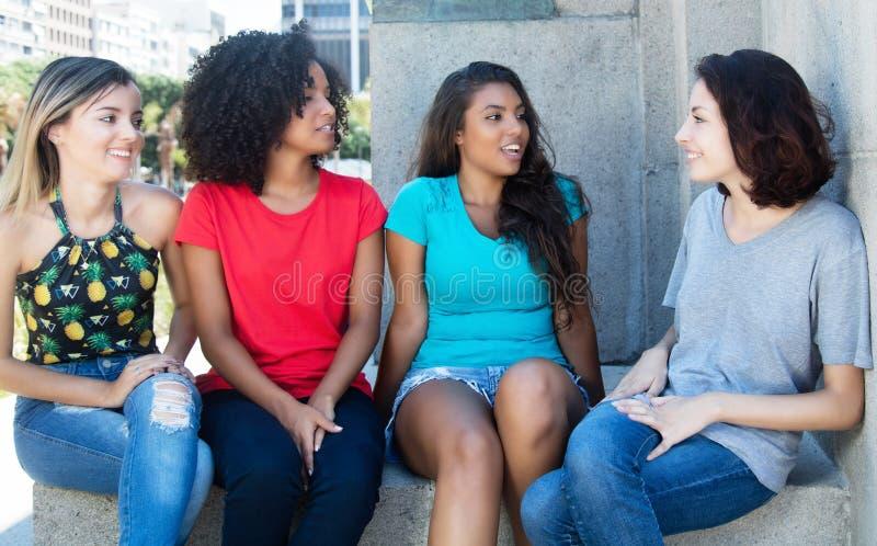 Gruppo di conversazione e di rilassamento di giovane donna fotografia stock libera da diritti