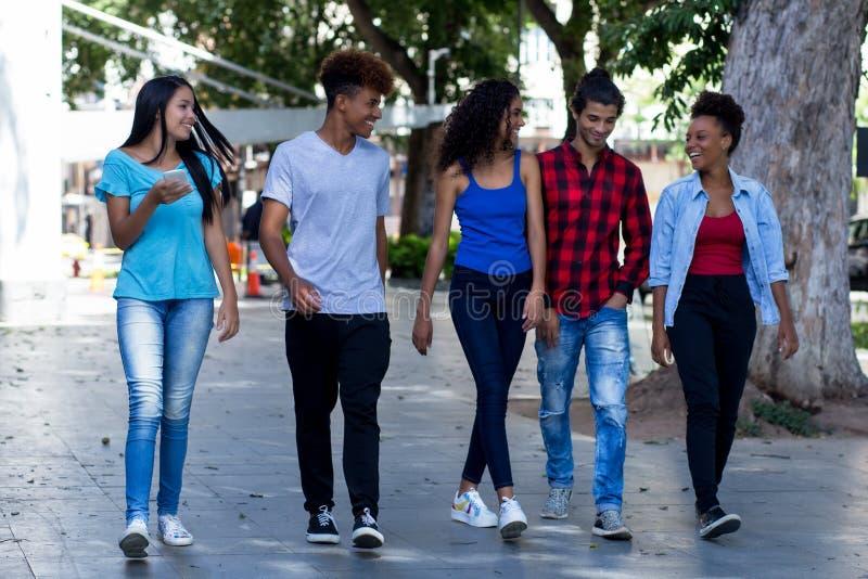 Gruppo di conversazione di giovani adulti dei pantaloni a vita bassa brasiliani e messicani in città immagine stock